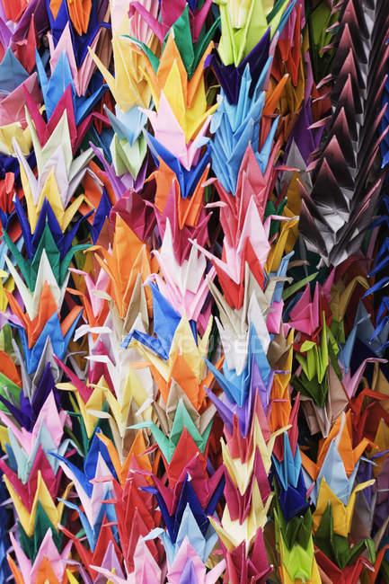 Primer plano de las grúas de origami japonesas tradicionales multicolores en la tienda de recuerdos, Kyoto, Japón - foto de stock