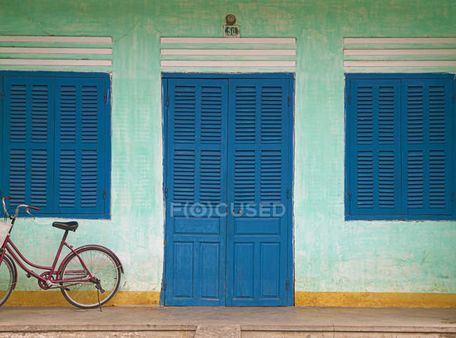 Bike parked on front porch with blue wooden door and windows — Stock Photo