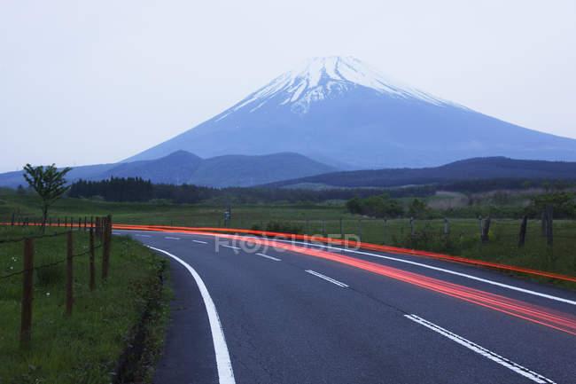 Blurred headlights on road before mountain, Japan — Stockfoto