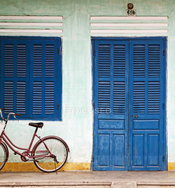 Bicicletta parcheggiata sul portico anteriore con porta e finestra in legno blu — Foto stock