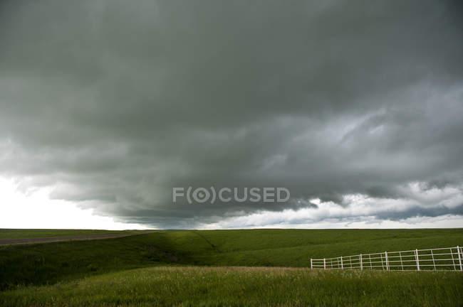 Nuvens de tempestade sobre a paisagem rural com cerca no campo — Fotografia de Stock