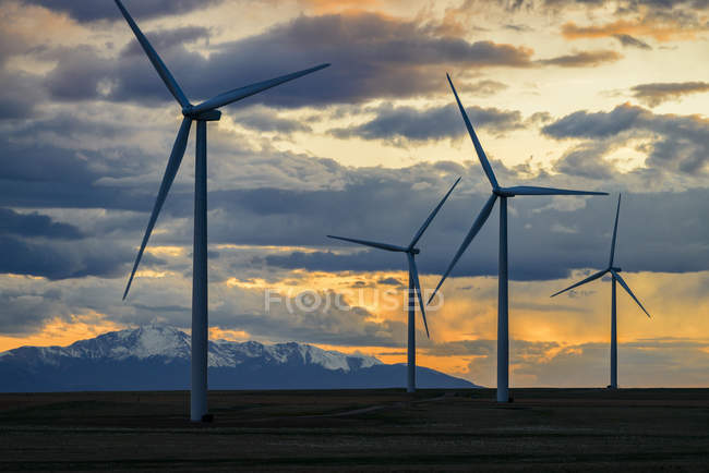 Wind turbines at sunset with clouds in dramatic sky, Colorado, USA — Stock Photo