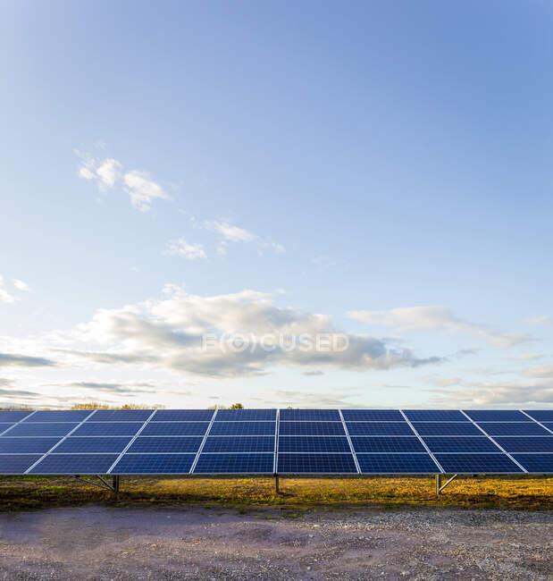 Painéis solares sob céu azul em paisagem remota — Fotografia de Stock