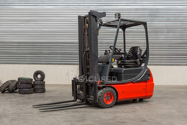 Forklift machinery parked in warehouse interior — Stock Photo