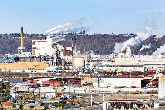 Humo que fluye de las pilas de humo en el área industrial - foto de stock
