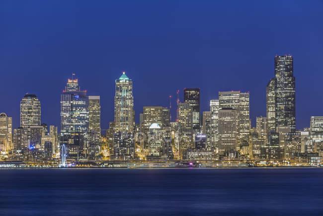 Paisaje del horizonte de la ciudad iluminado por la noche, Seattle, Washington, Estados Unidos - foto de stock