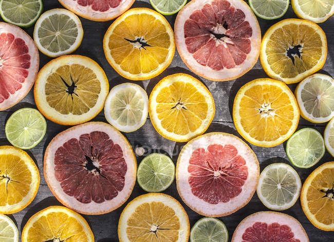 Variety of citrus fruit slices on rustic wooden background — стокове фото