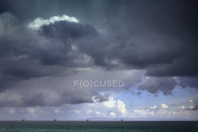 Stormy sky over oil drilling platforms in ocean — Stock Photo