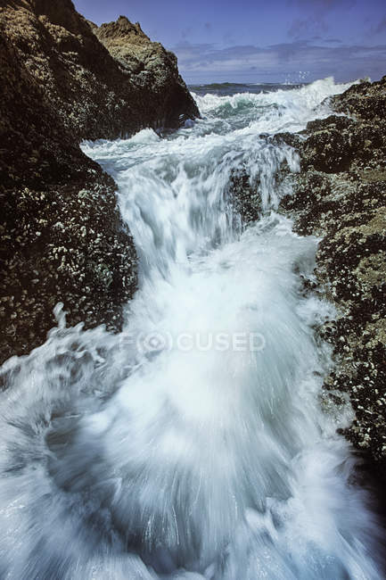 Blurred view of waves over big rocks on beach — Stock Photo