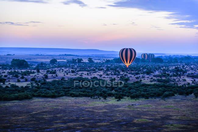 Globos de aire caliente volando sobre el paisaje de la sabana, Kenia, África - foto de stock
