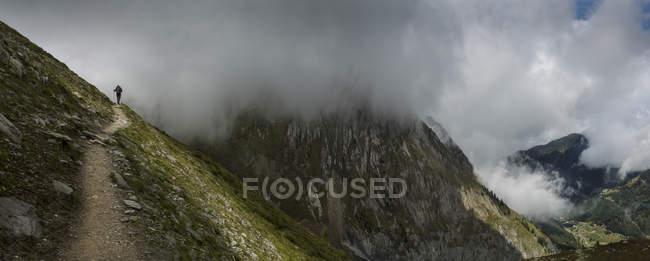 Silueta de excursionista en nubes en sendero de montaña, Monte Blanc, Suiza - foto de stock