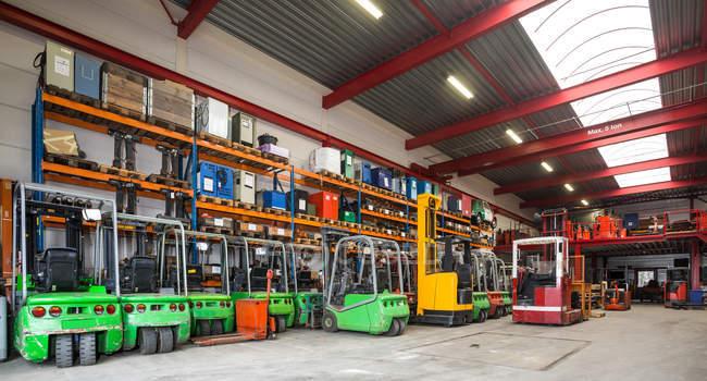 Вилочная техника припаркована в ряду на складе — стоковое фото