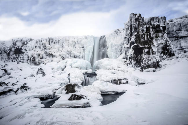 Waterfall pouring over icy cliffs in remote landscape — Foto stock