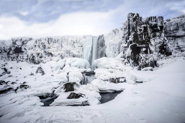 Cascata che si riversa su scogliere ghiacciate in un paesaggio remoto — Foto stock