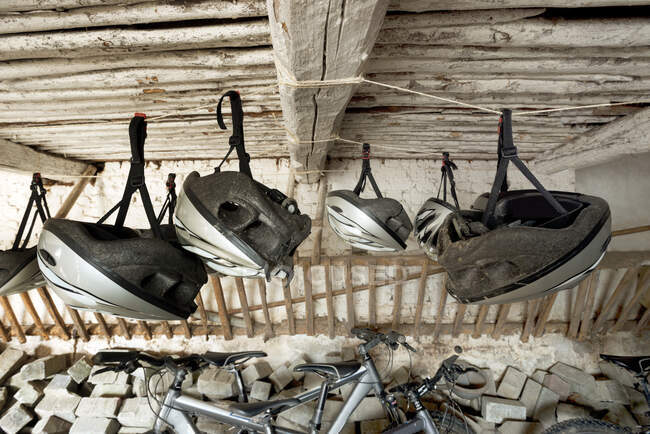 Bicycle helmets hanging from wooden ceiling — Stock Photo