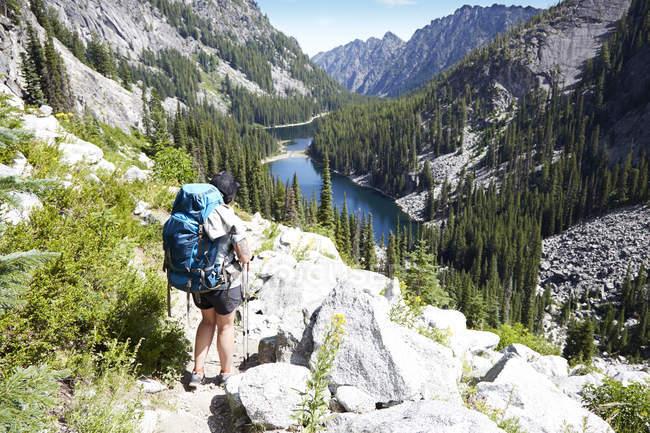 Weibliche Wandererin, die auf felsigem Hügel spazieren geht — Stockfoto