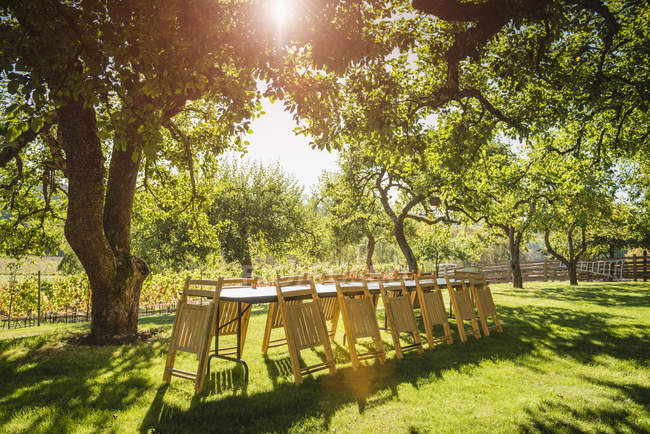Folded chairs leaning on table in backyard with backlit — Stock Photo