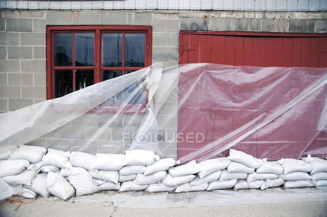 Bolsas de arena y lámina de plástico en la pared del edificio - foto de stock