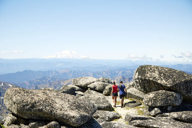 Couple hiking on rocky hilltop, Washington, USA - foto de stock