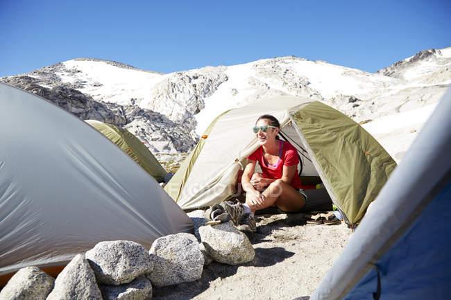 Caminhante feminino sentado na tenda no parque de campismo — Fotografia de Stock