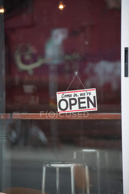 Close-up of open sign on glass cafe door — стокове фото