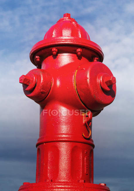Close-up of red fire hydrant against blue cloudy sky. — Stock Photo