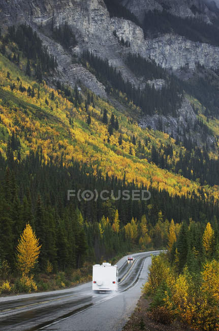 Motor home truck driving on road through remote mountains — Fotografia de Stock