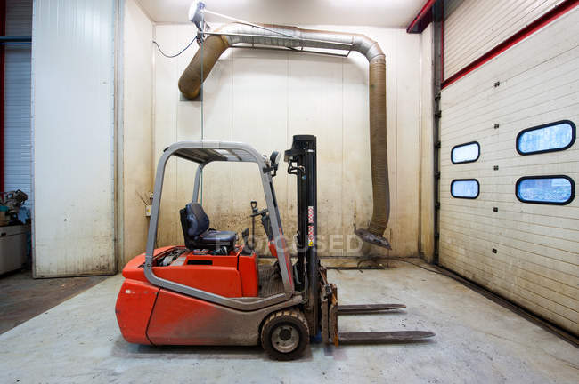 Forklift machinery parked in warehouse garage with metal door — Stock Photo