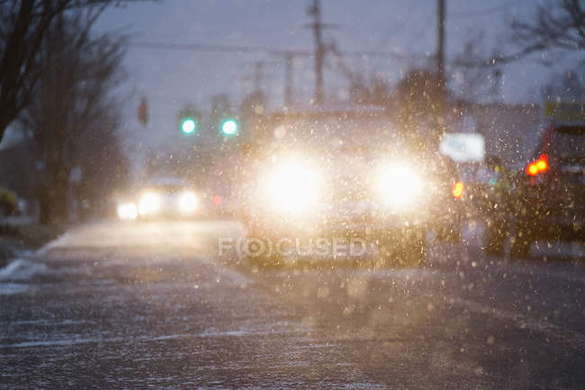 Cars driving on snowy urban street at night — Stock Photo