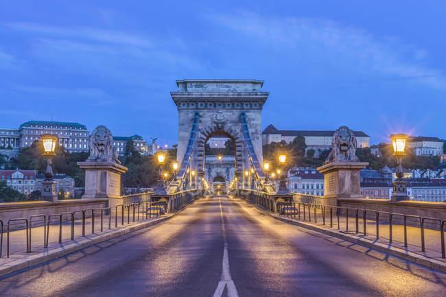 Львиные статуи и фонари вдоль Цепного моста, Будапешт, Венгрия — стоковое фото