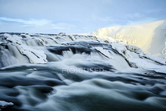 Flusswasser fließt über eisige Felsformationen — Stockfoto