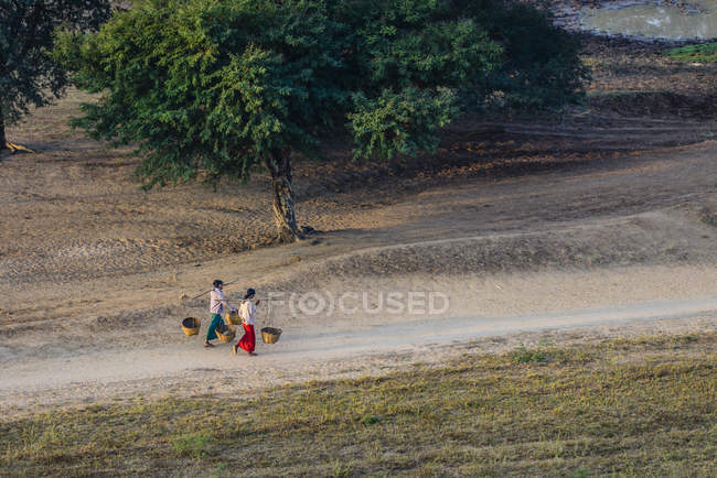 Local people carrying baskets on dirt path in rural landscape, Myanmar — Stock Photo