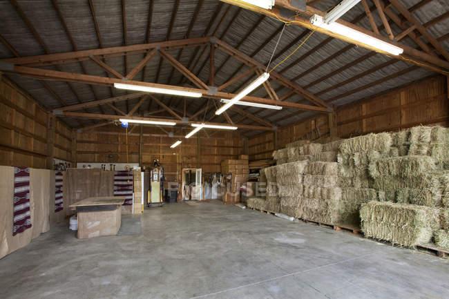 Hay bales stacked in farm barn interior — Stock Photo