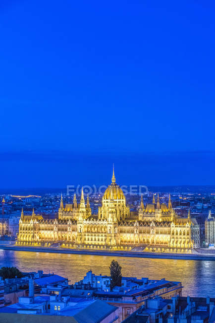 Aerial view of Parliament Building illuminated at dusk in cityscape of Budapest, Hungary — стокове фото