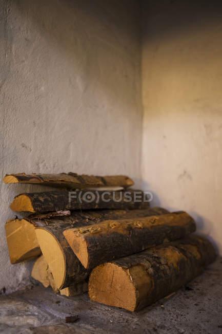 Primer plano de leña apilada en la esquina interior - foto de stock