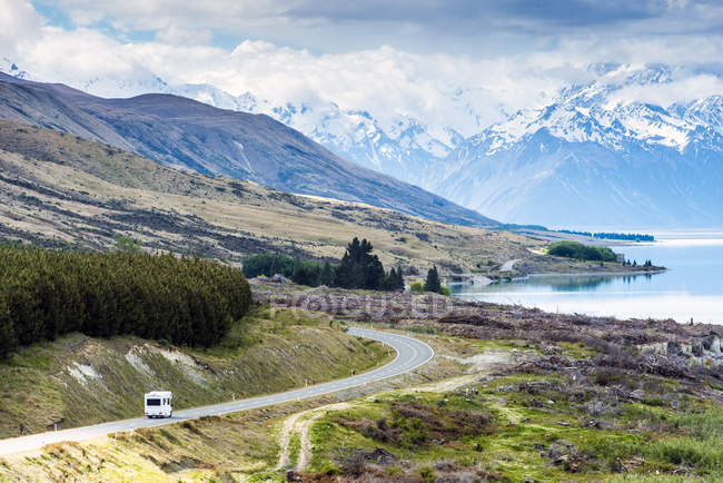 Auto driving near mountains and lake in remote landscape — Fotografia de Stock