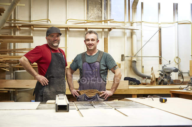 Two male carpenters smiling in workshop interior — Stock Photo