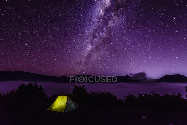 Milky Way galaxy over campsite in starry night sky — стокове фото
