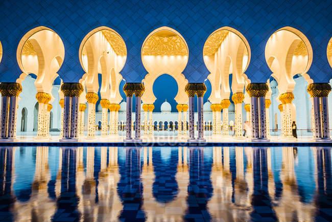 Ornate tiled arches of Grand Mosque illuminating at night, Abu Dhabi, United Arab Emirates - foto de stock