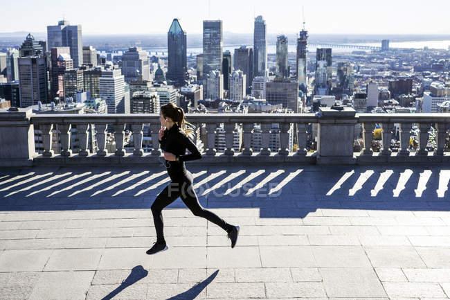 Кавказская женщина бежит в городе с небоскребами вдали, Монреаль, Канада — стоковое фото