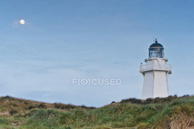 Lighthouse under moon in blue sky, Pacific Rim, New Zealand — Stock Photo