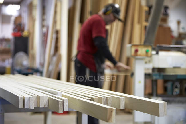 Carpenter standing and smiling in workshop interior — Stock Photo
