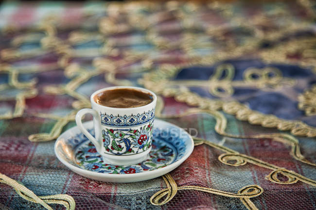 Close-up of cup of Turkish coffee on colorful tablecloth — Stock Photo