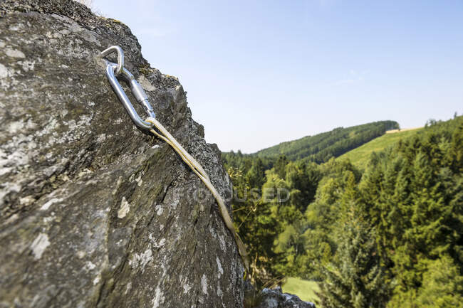 Carabiner on hook in steep rock face — Stock Photo
