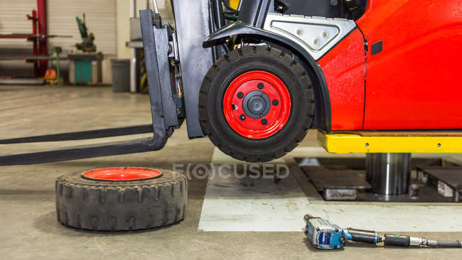 Forklift machinery on lift in garage interior — Stock Photo