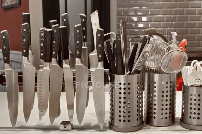 Cuchillos en estante magnético en cocina comercial - foto de stock