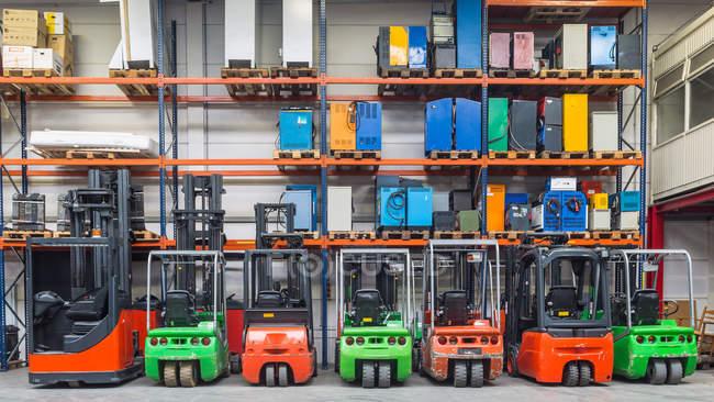 Máquinas de empilhadeira estacionadas em uma fileira no armazém — Fotografia de Stock