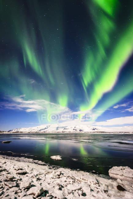 Northern lights reflecting in still remote river in Jokulsarlon lagoon, Iceland — Stock Photo
