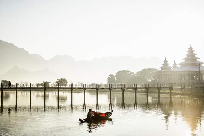 Montanhas e reflexão ponte em lago imóvel com barco com monge budista jovem e guarda-chuvas, Hpa-an, Kayin, Mianmar — Fotografia de Stock