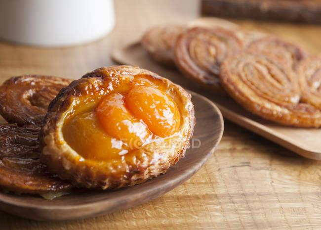 Закрытие абрикосового слоеного теста и пальмиерных кулинарных блюд на столе — стоковое фото